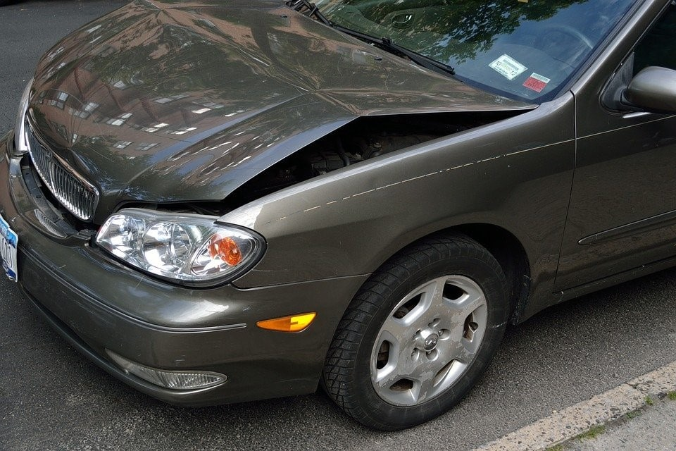 grey Nissan Maxima with a dented hood